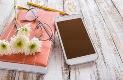 Fleur blanche et crayon sur le carnet avec le smartphone sur en bois merci Photos stock