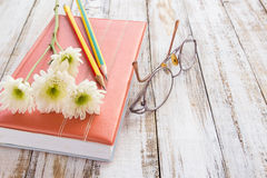 Fleur blanche et crayon sur le carnet sur la table en bois Image libre de droits