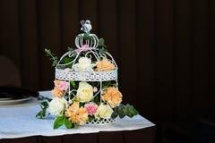 Fleur dans la cage à oiseaux sur la table avec des bougies Fond de Brown Photographie stock libre de droits