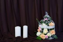 Fleur dans la cage à oiseaux sur la table avec des bougies Fond de Brown Photographie stock