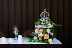 Fleur dans la cage à oiseaux sur la table avec des bougies Fond de Brown Image libre de droits