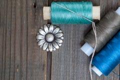 Fleur de bouton de vintage, bobine de fil et une aiguille de couture Images stock