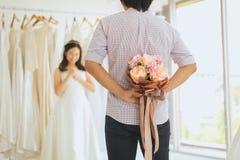 Fleur de dissimulation de marié derrière de retour afin d'étonner la jeune mariée, émotion positive de femme et faire face à heur photos libres de droits