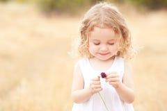 Fleur de fixation de petite fille Photos stock
