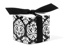 Fleur-de-lis Designed Gift Box. With attached black bow. White fleur-de-lis designs are on the black sides of the box. White background Royalty Free Stock Images