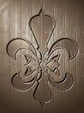 Fleur de lis relief on wooden background Royalty Free Stock Photos