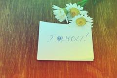 Fleur de marguerite et morceau de papier avec le texte Photographie stock libre de droits