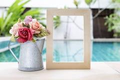 Fleur de papier de Rose dans le pot de bidon avec le cadre en bois au-dessus de la piscine brouillée Photographie stock