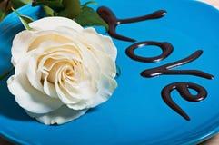 Fleur de rose de blanc d'un plat bleu avec amour d'inscription de chocolat, Image libre de droits
