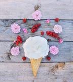 Fleur de rose de blanc et groseilles rouges mûres dans le cornet de crème glacée sur le fond en bois rustique image libre de droits