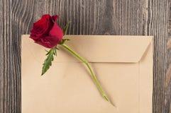 Fleur de rose de rouge sous enveloppe de papier déchirée Photos stock