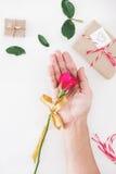 Fleur de Rose en main, avec le cadeau de valentines sur la table blanche Photographie stock libre de droits