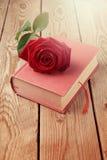 Fleur de Rose sur le livre au-dessus du fond en bois Photographie stock
