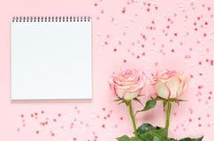 Fleur deux rose fraîche de floraison rose avec le bloc-notes sur le fond rose avec les coeurs colorés Photos stock