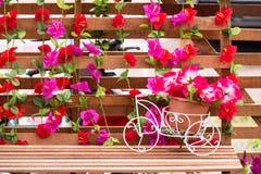 Fleur en plastique dans la bicyclette de blanc de pot Photographie stock libre de droits