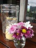 Fleur et bougie roses dans le pot en verre Photo stock