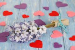 Fleur et coeurs pourpres de jacinthe sur les planches en bois bleues minables dans le style rustique Photos stock