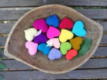 Fleur et feuille en baisse sur les coeurs colorés dans le plateau en bois dans le jardin Photos stock