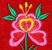 Fleur faite main de broderie sur le velours rouge Photo libre de droits