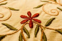 Fleur, feuilles de vert et tiges rouges avec des boucles, brodées avec le point de satin Photos stock