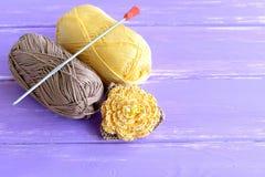 Fleur jaune et brune faite main de crochet décorée des perles Deux écheveaux de fils de coton et de crochet de crochet sur le fon Photographie stock libre de droits
