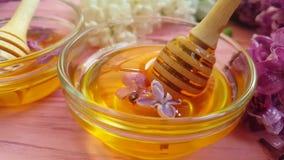 Fleur lilas délicieuse de versement naturelle organique de miel sur le fond en bois savoureux banque de vidéos