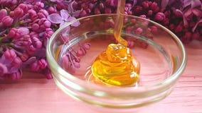 Fleur lilas de versement naturelle organique de miel sur le fond en bois savoureux banque de vidéos
