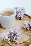 Fleur lilas et une tasse de thé sur le bureau de livraison en bois Fond blanc Images stock