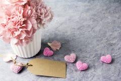 Fleur rose d'oeillet dans la tasse blanche avec l'étiquette vide de papier brun Photo stock
