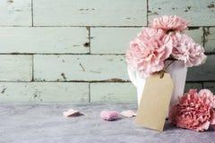 Fleur rose d'oeillet dans la tasse blanche avec l'étiquette vide de papier brun Photos stock