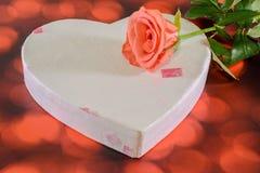 Fleur rose d'orange avec le boîte-cadeau de forme de coeur, fond rouge de bokeh Photos stock