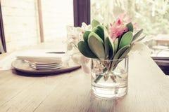 Fleur rose dans le vase en verre sur la table dinning en bois Photographie stock