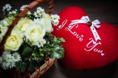 fleur rose de bouquet à un coeur de panier et d'oreiller Images stock