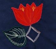 Fleur rouge avec la feuille Applique sur le tissu bleu Photo libre de droits
