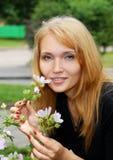 Fleur sentante de belle fille Photographie stock