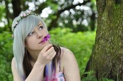Fleur sentante de fille Photographie stock