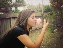 Fleur sentante de fille Images stock