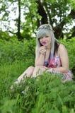 Fleur sentante de fille dans la forêt Images stock