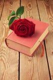 Fleur simple de rose de rouge sur le livre au-dessus du fond en bois Photographie stock