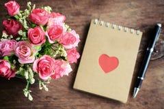 Fleurissez avec le bloc-notes et le stylo vides sur le vieux fond en bois Photos libres de droits