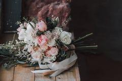 Fleurissez la composition avec les roses blanches et roses et d'autres fleurs sur une table rustique dessin-modèle Photos stock