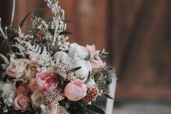 Fleurissez la composition avec les roses blanches et roses et d'autres fleurs sur une table rustique dessin-modèle indoors Photos stock