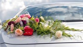 Fleurissez la décoration et un anneau réglé sur le capot gris de voiture de mariage Photos stock