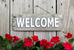 Fleurissez la frontière des roses rouges par le signe bienvenu en bois accrochant sur la barrière en bois distresed Photos libres de droits