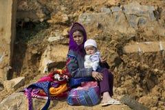 Fleurissez la grand-mère de Hmong s'asseyant au soleil sur la roche avec le bébé potelé sur ses genoux image stock