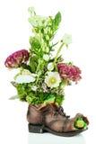 Fleurissez la pièce maîtresse de disposition de bouquet dans la vieille chaussure avec des grenouilles Photographie stock