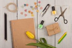 Fleurissez la tulipe, le bloc-notes vide, les ciseaux, le vernis à ongles et les boutons sous forme de coeurs Images stock