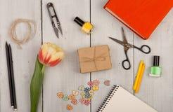 Fleurissez la tulipe, le bloc-notes vide, les ciseaux, le vernis à ongles et les boutons sous forme de coeurs Photos libres de droits