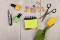Fleurissez la tulipe, le bloc-notes vide, les ciseaux, le vernis à ongles et les boutons sous forme de coeurs Image stock