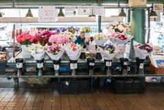 Fleurissez le vendeur derrière des bouquets sur le marché de place de Pike Image libre de droits
